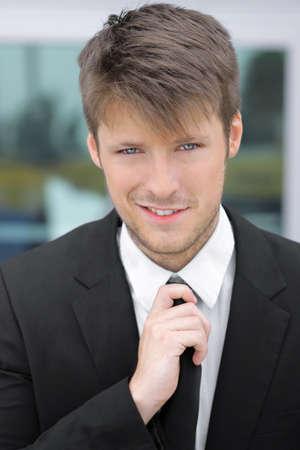 ビジネス スーツとネクタイで幸せな若い魅力的な男の肖像