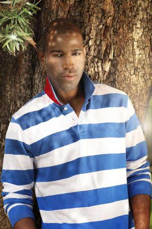 Openlucht voorjaar portret van een knappe jonge mannelijke model tegen boom