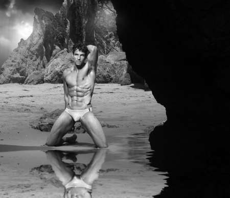 nue plage: Classique en noir et blanc portrait pittoresque de l'homme musculaire belle plage de rochers � Banque d'images