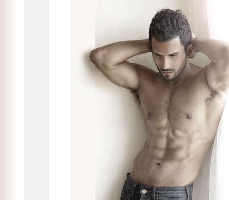 cuerpos desnudos: Hermosa modelo musuclar masculino con abs agradable en jeans cerca de la ventana con copia espacio