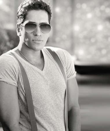 young male model: Hermoso fresco joven modelo masculino llevaba camiseta blanca y tirantes con gafas de sol