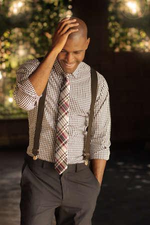 mannequin africain: Sexy intelligent jeune homme d'affaires moderne avec un sourire agr�able � regarder vers le bas et la main sur la t�te Banque d'images