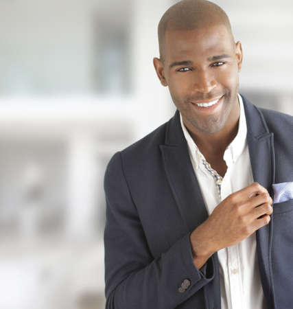 Portrait of a happy young fashionable businessman smiling with copy space