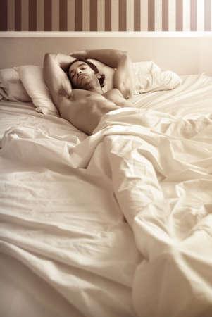 Sensual portrait d'un modèle masculin nu sexy magnifique pose dans son lit Banque d'images