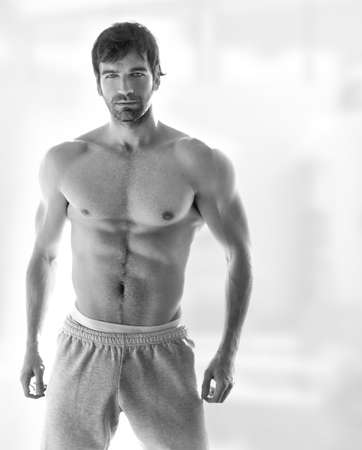 man underwear: Sexy portrait of a very muscular hot shirtless male model in in sweatpants with copy space