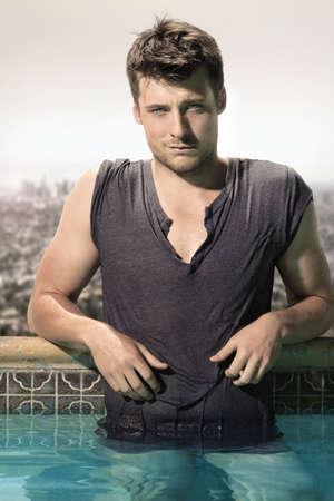 tremp�e: Mode portrait d'un superbe mod�le masculin dans tremp�e mouill�e t-shirt debout dans la piscine de luxe
