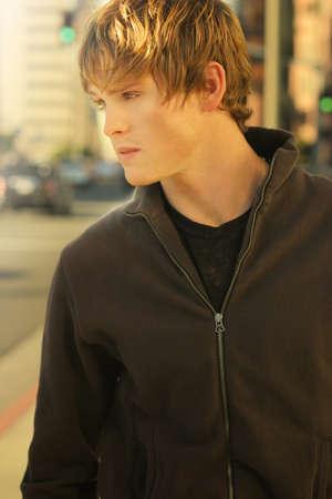 Outdoor portrait d'un jeune homme décontracté dans la ville chaude lumière dorée