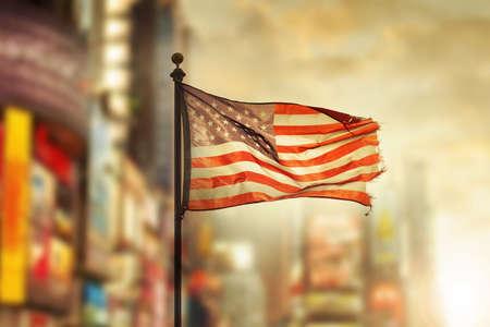 Flarden Amerikaanse vlag waait in de wind tegen koele stad vage achtergrond Stockfoto