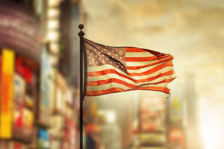 Tattered American flag blowing in the wind against cool city blurred background Standard-Bild