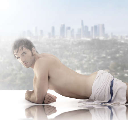 Beautiful male model wrapped in towell laying down against scenic city view background photo