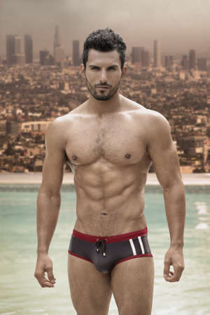 glamours: Sexy male model with great body and abs at pool with city in background Stock Photo