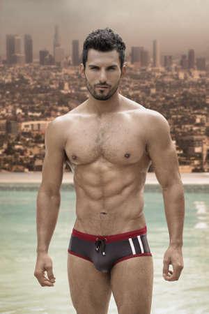 Sexy mannelijk model met grote lichaam en abs op zwembad met stad op de achtergrond