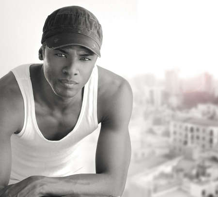 Portrait of a cool young man leaning on chair in white tank and trendy cap photo