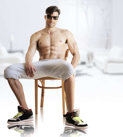 cocky: Portrait of a hot muscular male model shirtless in sunglasses in modern bright studio interior Stock Photo