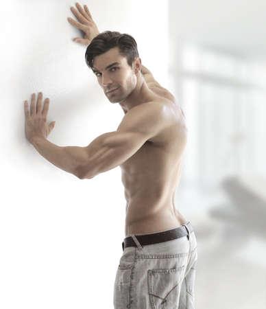 Portrait d'un homme torse nu sexy musculaire tournant dans un cadre moderne et lumineux, avec copie espace Banque d'images