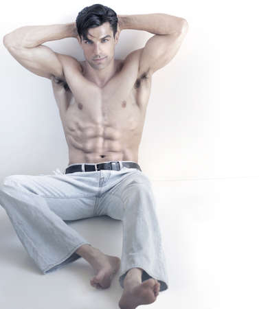 Cool toned portrait of a sexy muscular buff young male model shirtless in denim jeans relaxing with copy space and white background photo