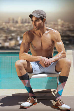 Fashion portrait of shirtless male model at pool with retro cool look and styling photo