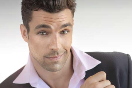 Portret van een sexy speelse mannelijk model in pak met leuke vertrouwen meningsuiting tegen neutrale achtergrond