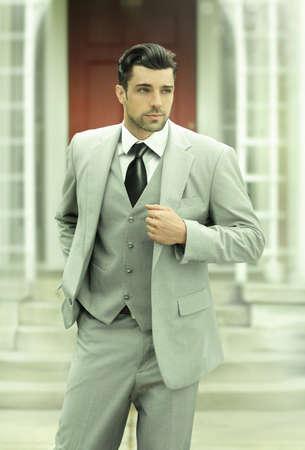 Gestileerde mode-business full length portret van een succesvolle zelfverzekerde man in pak en stropdas