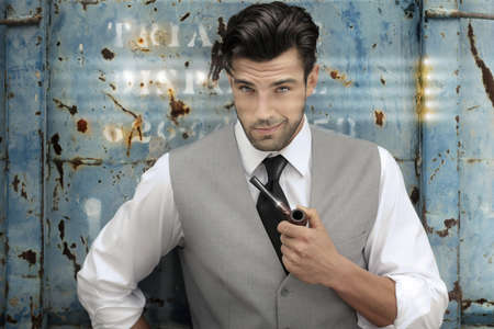 man in suit: Portrait of a confident classically handsome male model holding a pipe in upscale clothing  Stock Photo