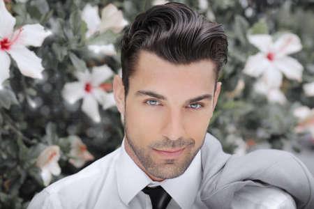 Begrip portret van een mooie jonge man tegen de achtergrond van bloemen Stockfoto