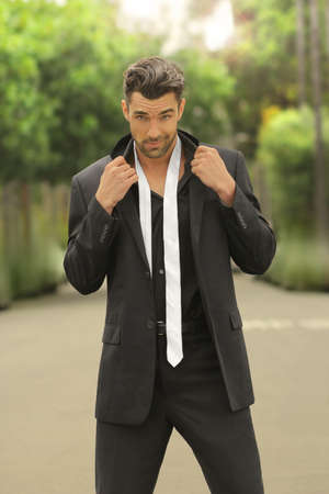 Fashion portrait of a sexy male model in black suit with loose white tie Standard-Bild