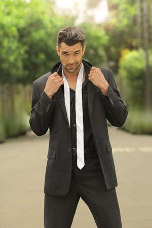 Fashion portret van een sexy mannelijk model in zwart pak met losse witte stropdas