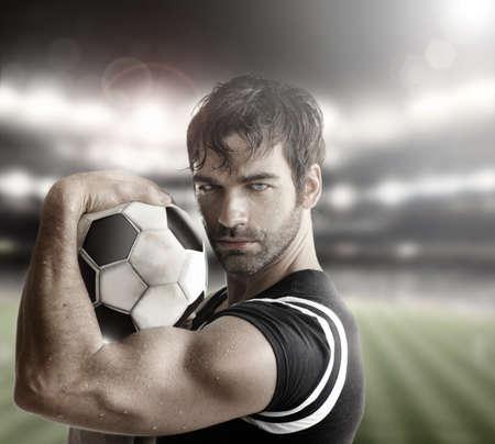 Sexy gespierde man atleet met bal Stockfoto