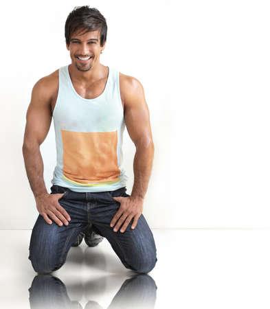 Sexy modèle masculin occasionnel souriant flirter sur fond blanc