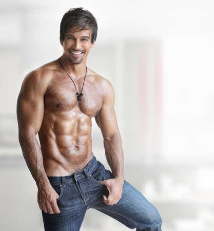 Sexy modèle masculin torse nu sourire avec un corps musclé et abs contre un fond blanc