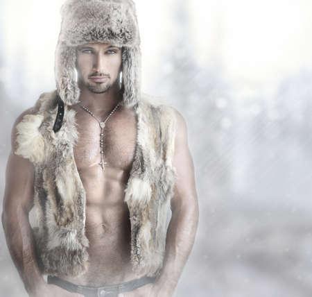 torso nudo: Ritratto di moda di un bel modello maschile in pelliccia cappello e giubbotto contro sfondo moderno