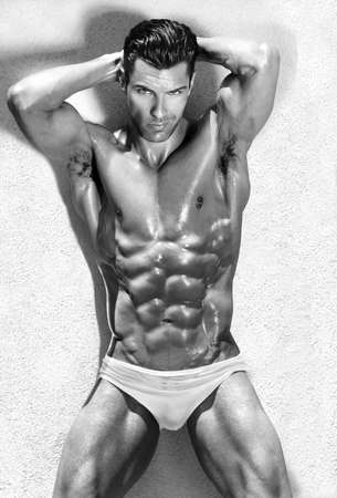 naked abs: Body portrait of a beautiful muscular male model in sensual sexy pose