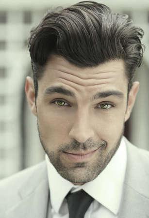 Close-up portrait stylisé d'un jeune homme d'affaires beau en costume avec une expression de plaisir ludique