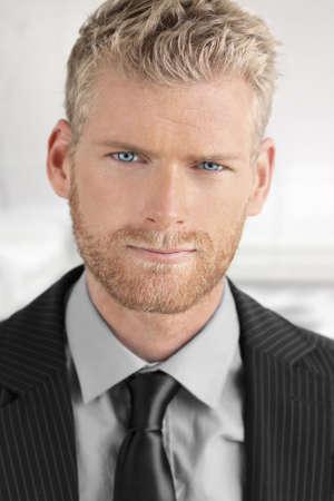 Modieuze jonge knappe zakenman met mooie blauwe ogen in pak