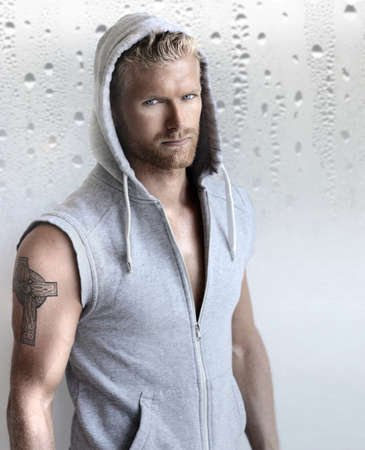 Sexy young fit man in hooded training vest against modern studio background Foto de archivo