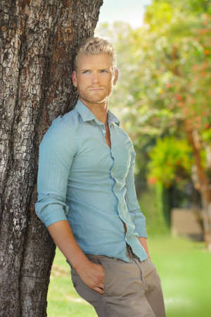Portrait of a beautiful young male model leaning against tree outdoors