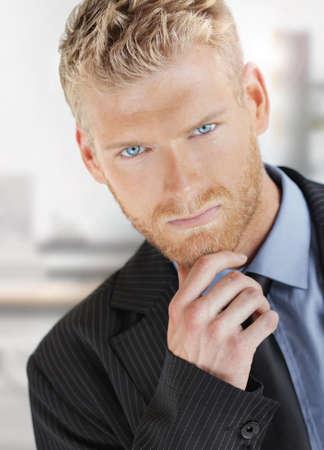 소송에서의 멋진 푸른 눈을 가진 유행 젊은 잘 생긴 비즈니스 남자