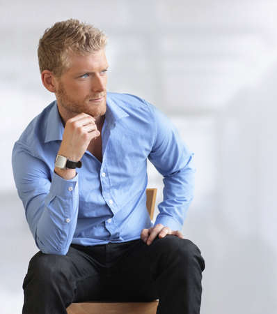 looking at watch: Handsome young businessman sitting