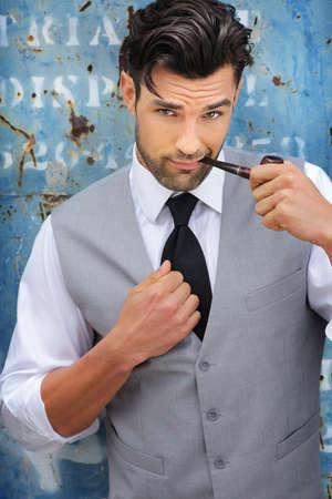 Portrait d'un modèle masculin classique beau confiant tenant une pipe dans les vêtements haut de gamme