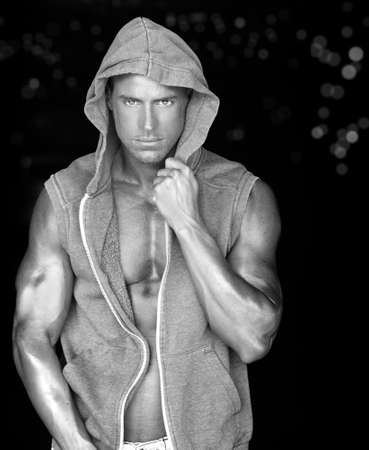 male grooming: Sexy young fit man in hooded training vest