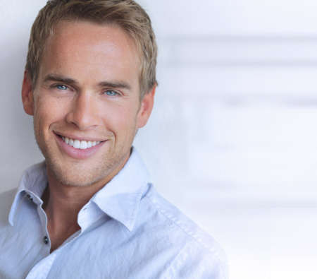 Portrait of a great looking confident young man with big real smile Standard-Bild