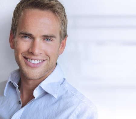 lächeln: Portrait eines großen schauenden selbstbewussten jungen Mann mit großen echtes Lächeln