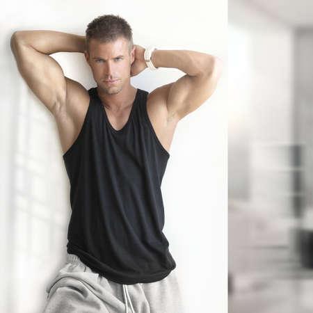Portret van sexy spier man die in moderne studio Stockfoto