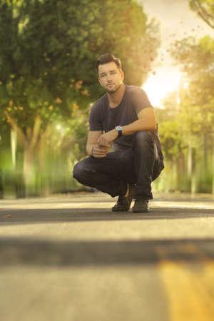 arrodillarse: Retrato al aire libre de un hombre joven casual en la calle Foto de archivo