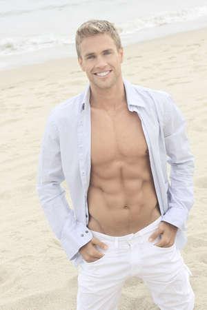 Lifestyle portret van een gelukkig succesvolle zelfverzekerde jonge man op het strand met open overhemd Stockfoto