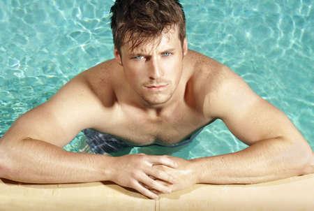 Summer portrait d'un jeune mec cool beau dans la piscine