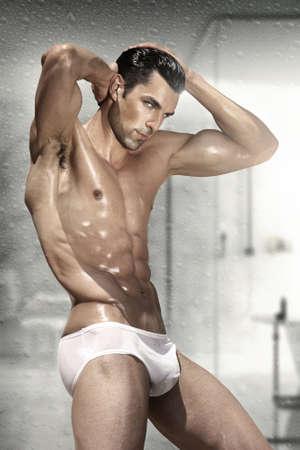 Beau jeune homme et attrayant avec le corps mouillé musculaire