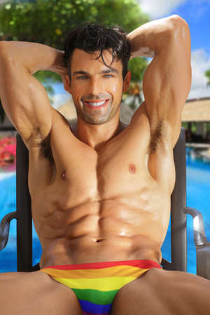 Smiling happy beautiful muscular man in rainbow swimtrunks in vibrant resort setting