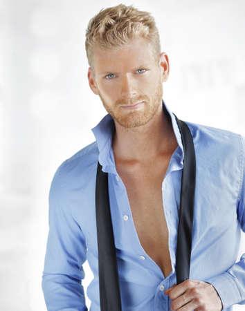 잘 생긴 멋진 남자가 자신의 셔츠를 열고 넥타이 unloosening의 초상화 스톡 콘텐츠