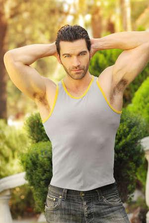 muscle shirt: Retrato al aire libre de un hombre joven y sano ajuste en camisa y pantalones vaqueros musculares Foto de archivo